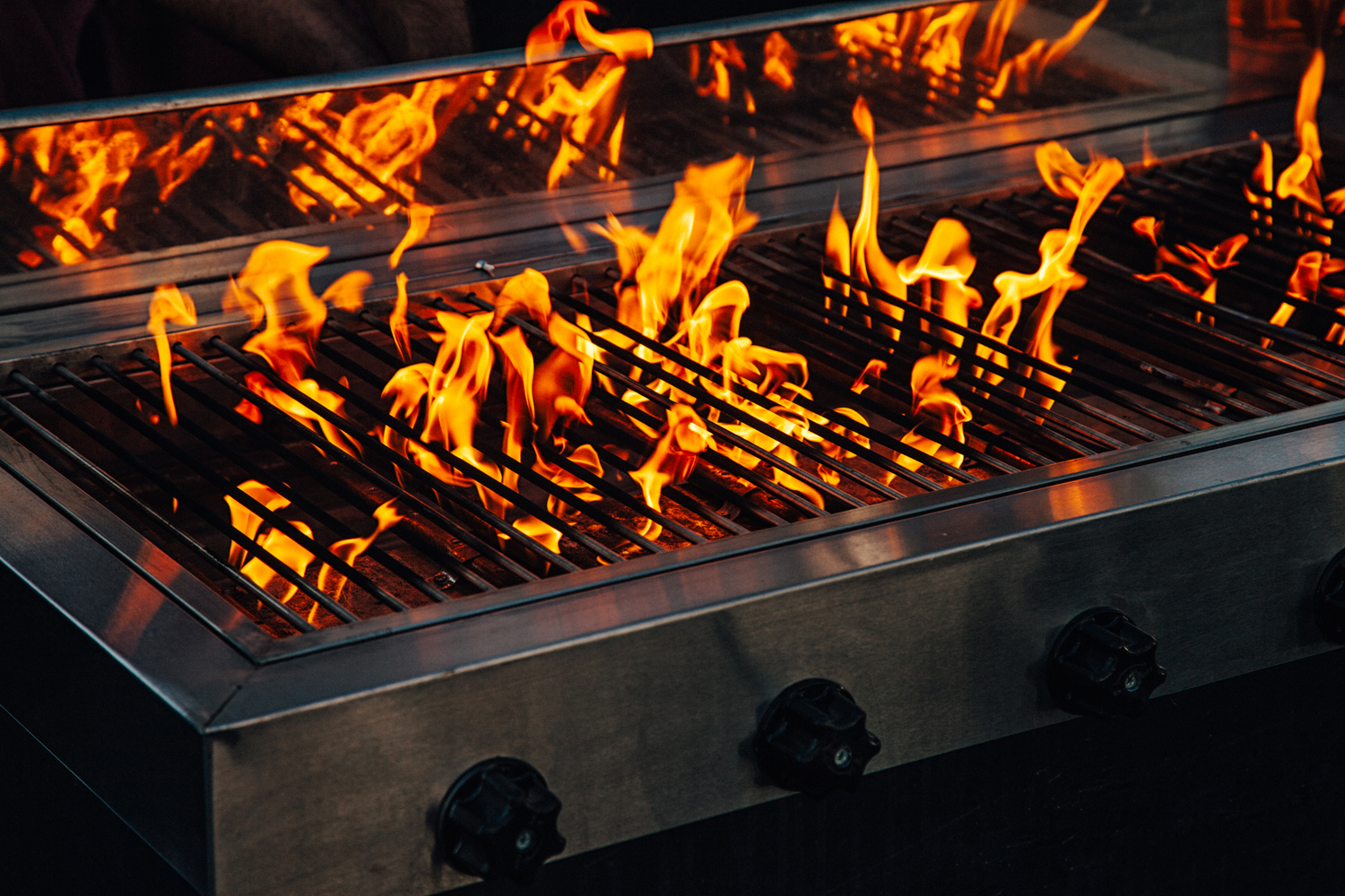 Hot Barbeque gas gril with bright yellow flames angburning coals. Working with music sound equalizer system.